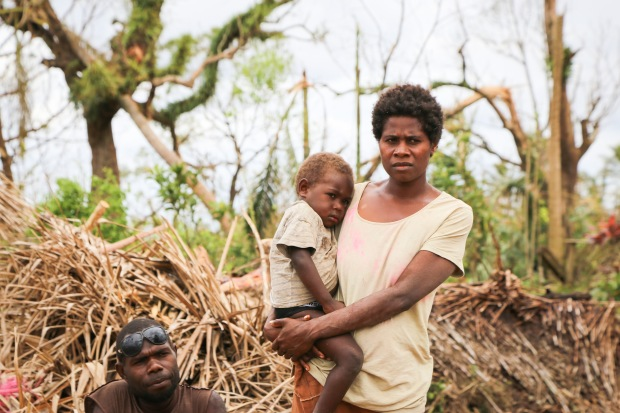Masau Kinia and his wife Nalin stand on the wreckage of their home (1)