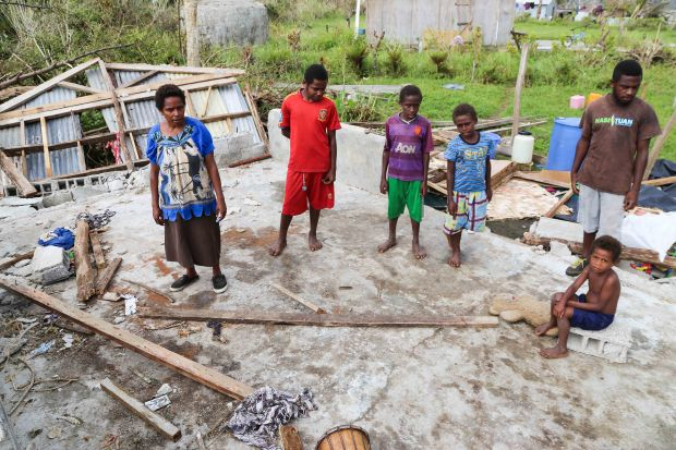 May Isaiah and her family stand amidst the rubble of what used to be their home