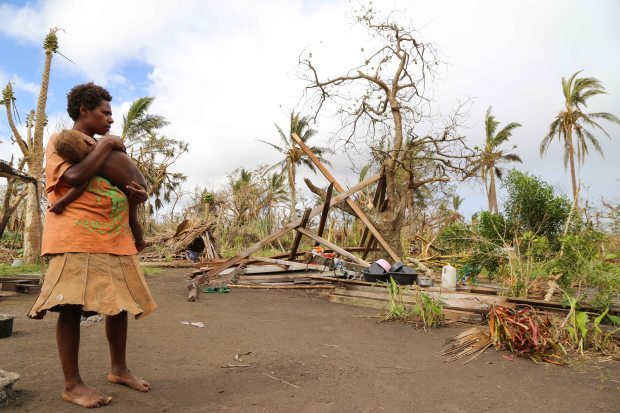 VUT-TFNZ-15-Helen Manson - day 3 stories -Sylvie Daniel holds her small baby on her compound where they lost every single building to Cyclone Pam including their house with a tree through the middle on Tanna Island